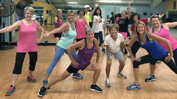 Zumba at Vermont Sport & Fitness club. 8 women posing after a great class at the gym
