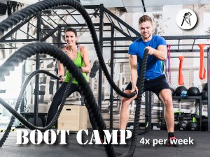 Two people using battle ropes in a boot camp style fitness class.